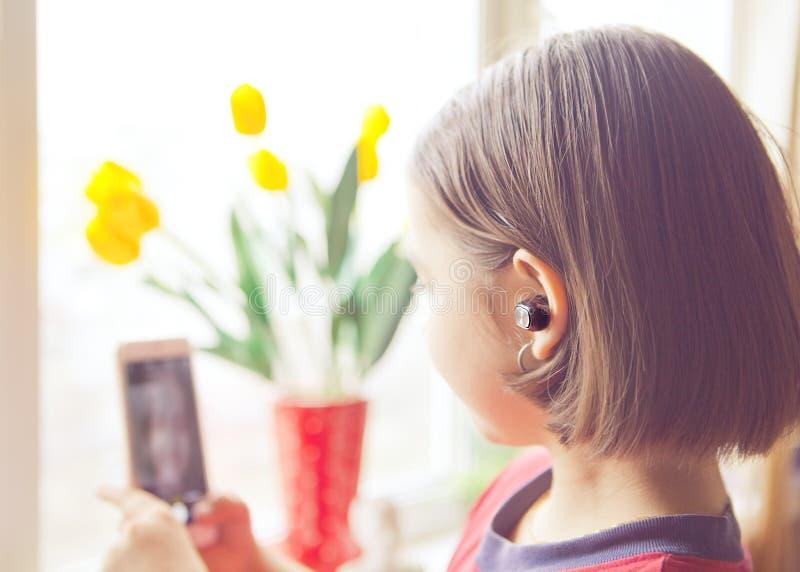 Dziewczyna z bezprzewodowym earpiece w twój ucho z telefonem w jego ręce i obrazy royalty free