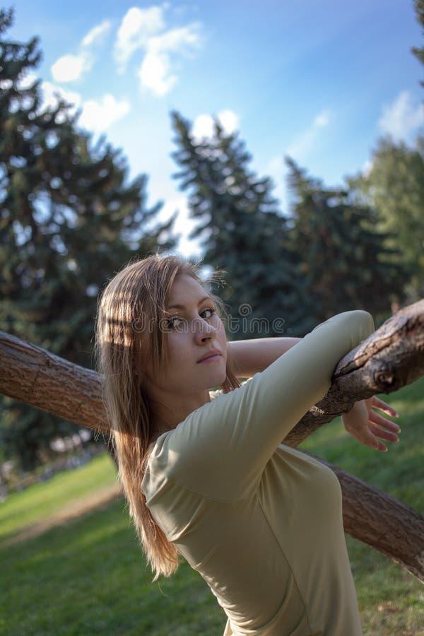 Dziewczyna z bieżącymi włosów stojakami blisko drzewa na tle jedlinowi drzewa fotografia stock