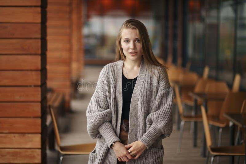Dziewczyna z blondynem i niebieskimi oczami w białej kurtce czarnej bluzce blisko lato kawiarni i stoi telefon i trzyma obraz stock