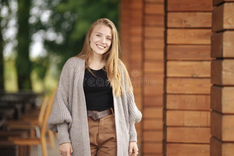 Dziewczyna z blondynem i niebieskimi oczami w białej kurtce czarnej bluzce blisko lato kawiarni i stoi telefon i trzyma zdjęcia royalty free