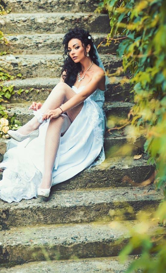 Dziewczyna z bridal fryzurą i makeup Kobiety odzieży koronki podwiązka na nodze Seksowna kobieta w pończochy bieliźnie na dniu śl fotografia stock