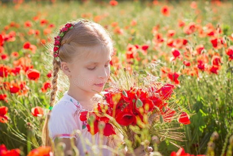 Dziewczyna z bukietem wśród maczka pola przy sinset zdjęcie stock