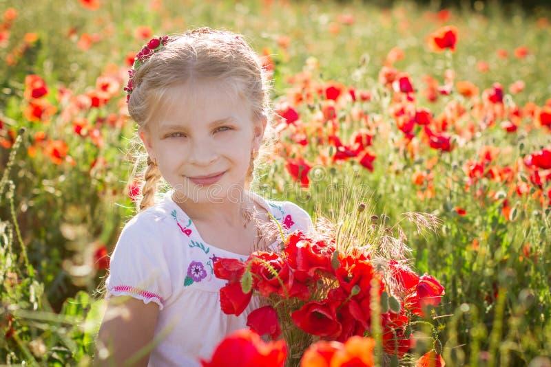 Dziewczyna z bukietem wśród maczka pola przy sinset obraz royalty free