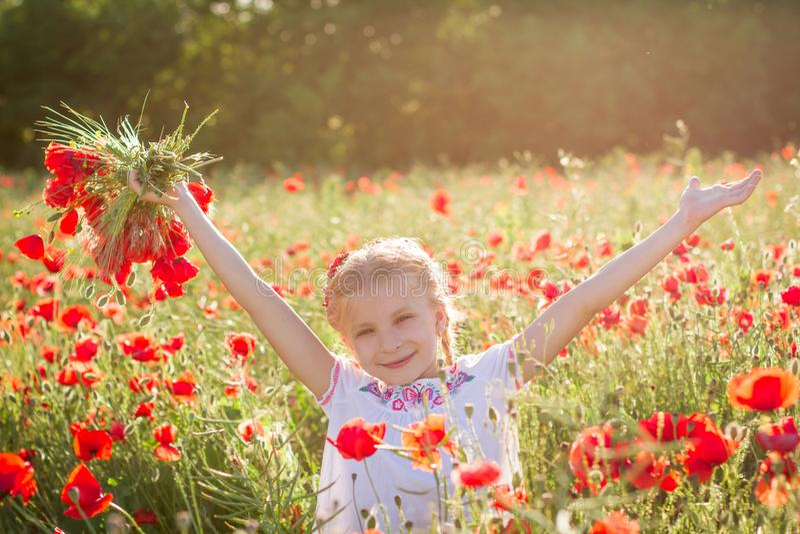 Dziewczyna z bukietem wśród maczka pola przy sinset zdjęcia stock