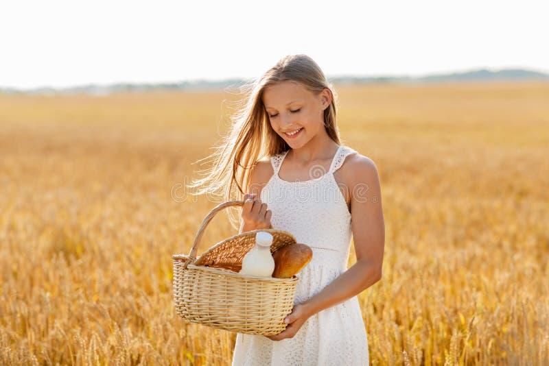 Dziewczyna z chlebem i mlekiem w koszyku na polu zbóż fotografia royalty free