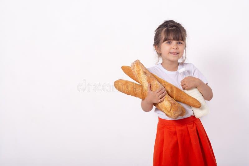 Dziewczyna z chlebem i mlekiem w ręce Świeżo piec chleb w rękach od piekarni Dziecko trzyma mnóstwo chleb w rękach obraz royalty free