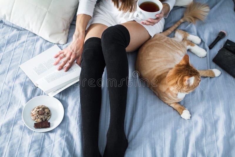 Dziewczyna z ciepłymi skarpetami z filiżanką herbata, kot, zamyka książkę obrazy royalty free