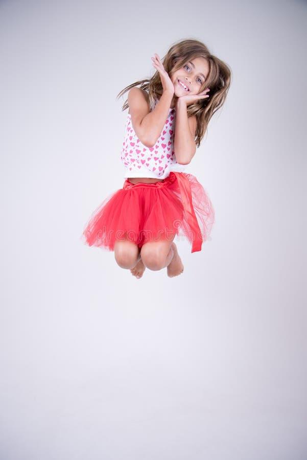 Dziewczyna z czerwieni spódnicy skakać szczęśliwy i ono uśmiecha się robić ślicznej twarzy zdjęcia royalty free