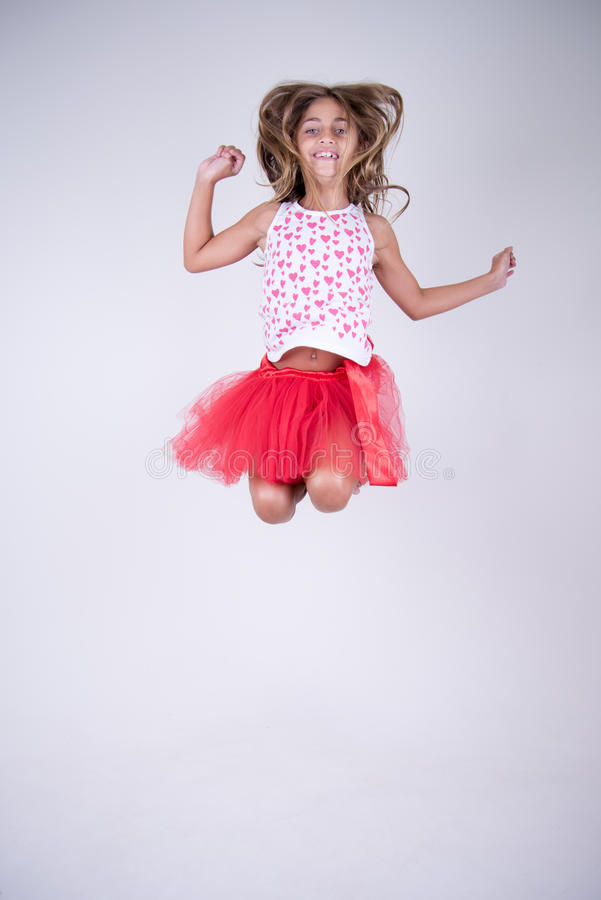 Dziewczyna z czerwieni spódnicy skakać szczęśliwy i ono uśmiecha się z rękami, up włosy w wiatrze i zdjęcie stock