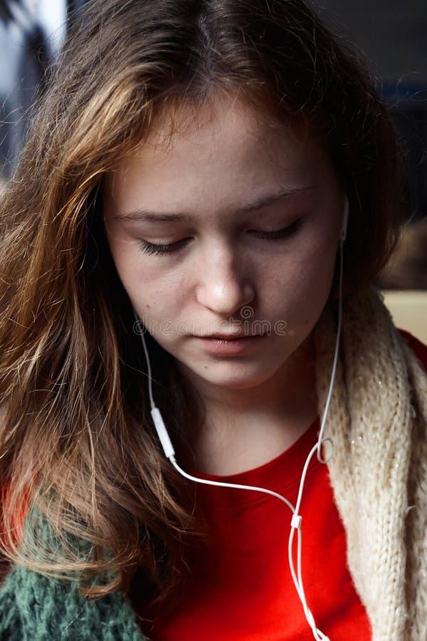 Dziewczyna z czerwonobrunatnym włosianym słuchaniem muzyka z jego przygląda się zamkniętego fotografia stock