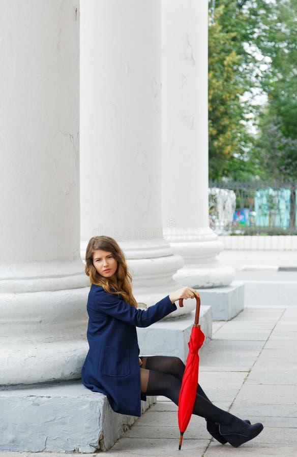 Dziewczyna z czerwonym parasolem siedzi thel kolumnami zdjęcia stock