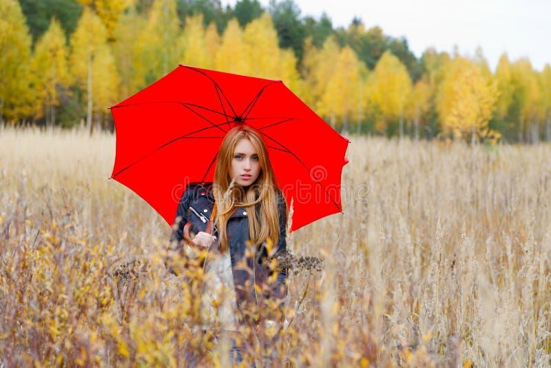 Dziewczyna z czerwonym parasolem w parku zdjęcia royalty free