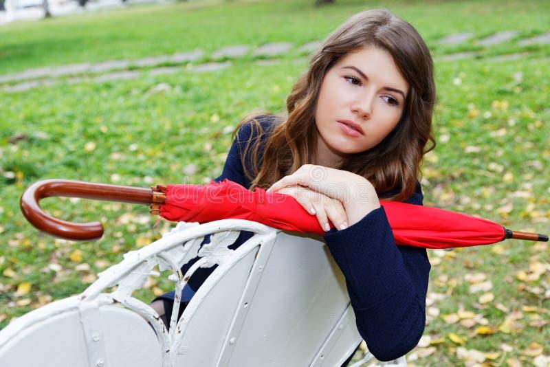 Dziewczyna z czerwonym parasolem w parku obraz stock