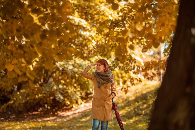 Dziewczyna z czerwonym parasolowym odprowadzeniem na jesieni miasta parku zdjęcia stock