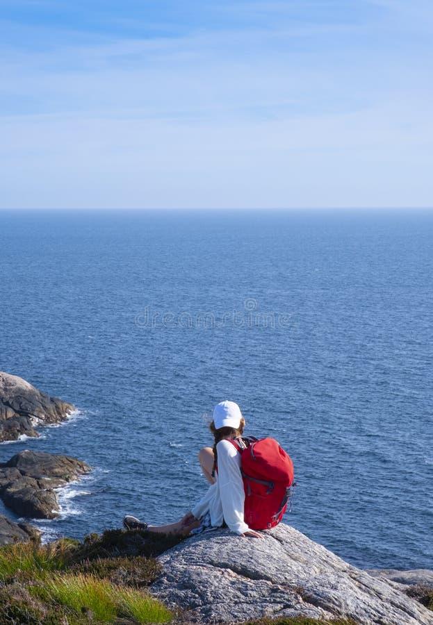 Dziewczyna z czerwonym plecakiem chodzÄ…ca po latarni morskiej Lindesnes obraz stock