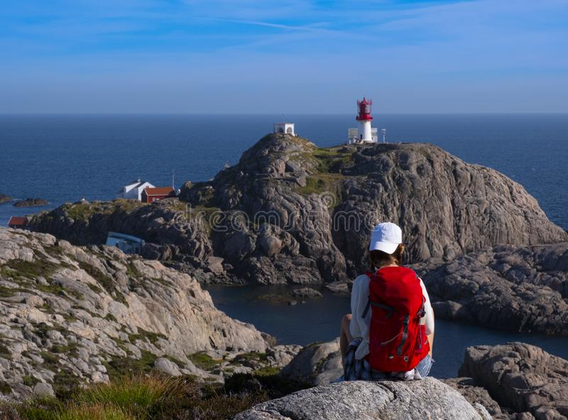 Dziewczyna z czerwonym plecakiem chodzÄ…ca po latarni morskiej Lindesnes zdjęcie royalty free