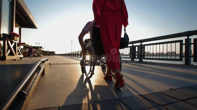 Dziewczyna Z Czerwonym włosy W pomarańcze sukni Stacza się Niepełnosprawnego faceta W wózku inwalidzkim Na nabrzeżu W zmierzchu obraz royalty free