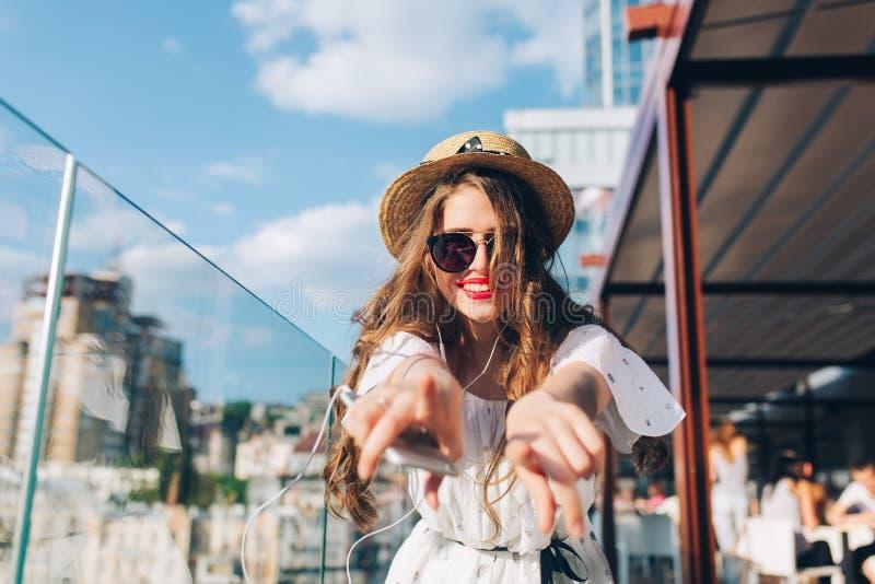Dziewczyna z długie włosy w okularach przeciwsłonecznych słucha muzyka przez hełmofonów na balkonie Jest ubranym białą suknię, po obrazy royalty free