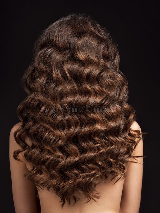 Dziewczyna z długim, kędzierzawym włosy, tylni widok Włosiana tekstura, w górę zdjęcia stock