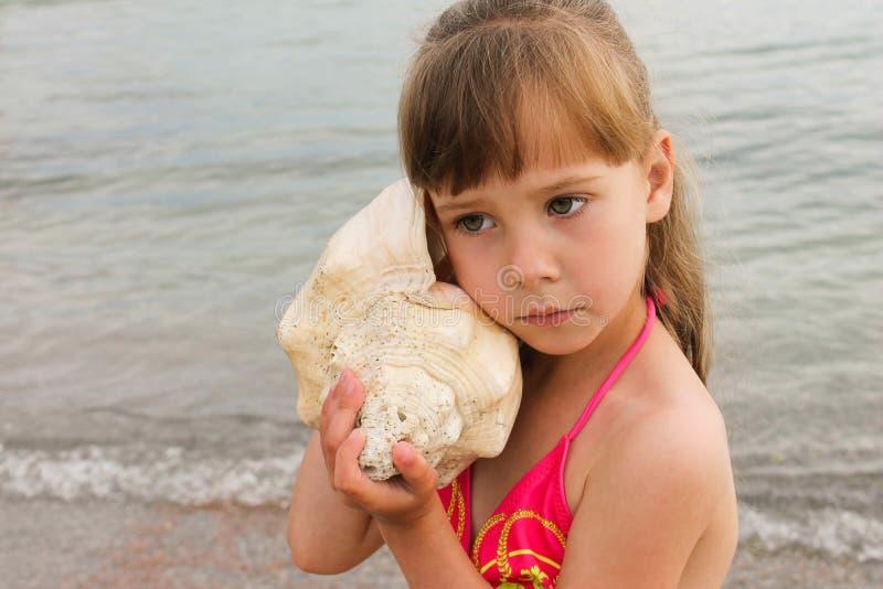 Dziewczyna z denną skorupą przy plażą obrazy stock