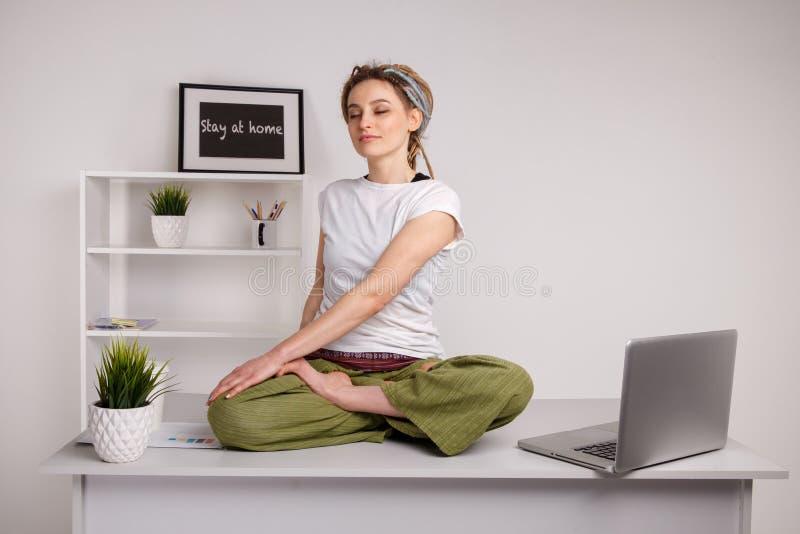 Dziewczyna z dreadlocks robi joga podczas pracowa? na laptopie zdjęcie stock