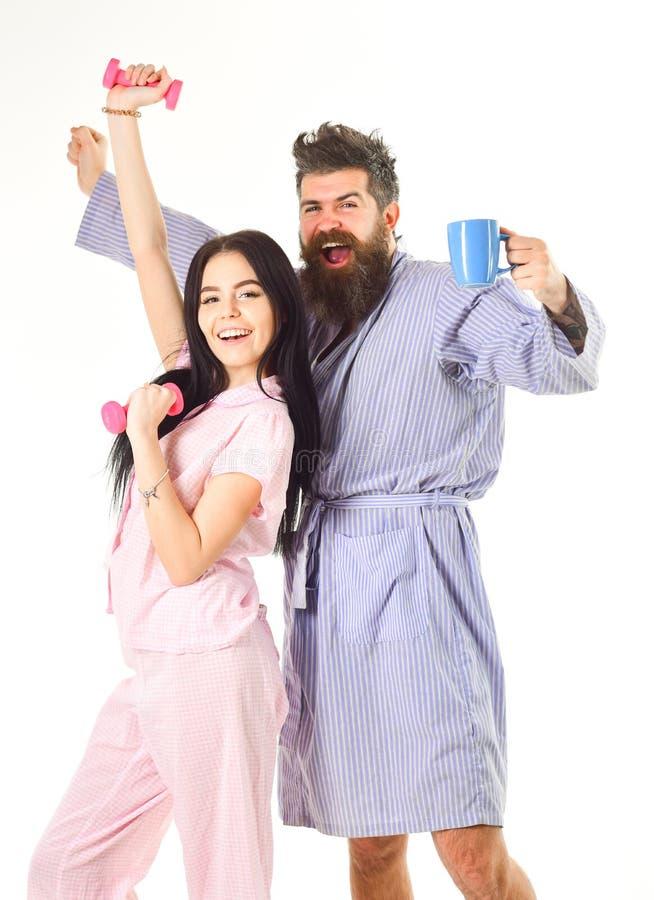 Dziewczyna z dumbbell, mężczyzna z filiżanką Dobiera się, rodzina na śpiących twarzach energia, pełno Para w miłości w piżamie fotografia royalty free