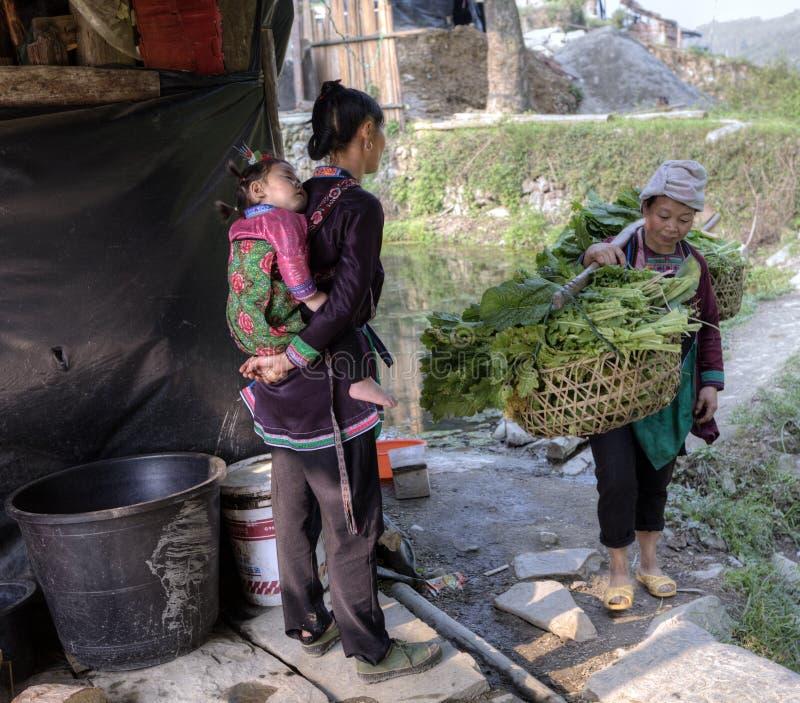 Dziewczyna z dzieckiem na ona z powrotem, spotykający kobiety przewożenia jarzmo obraz stock