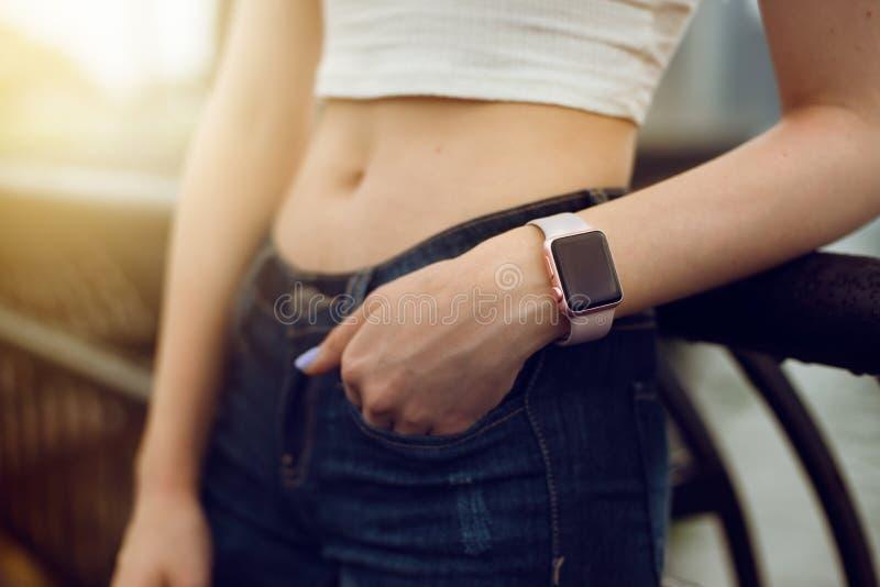 Dziewczyna z elektroniczną zegarka mienia ręką przy cajgami wkładać do kieszeni w mieście przy zmierzchu czasem obraz royalty free