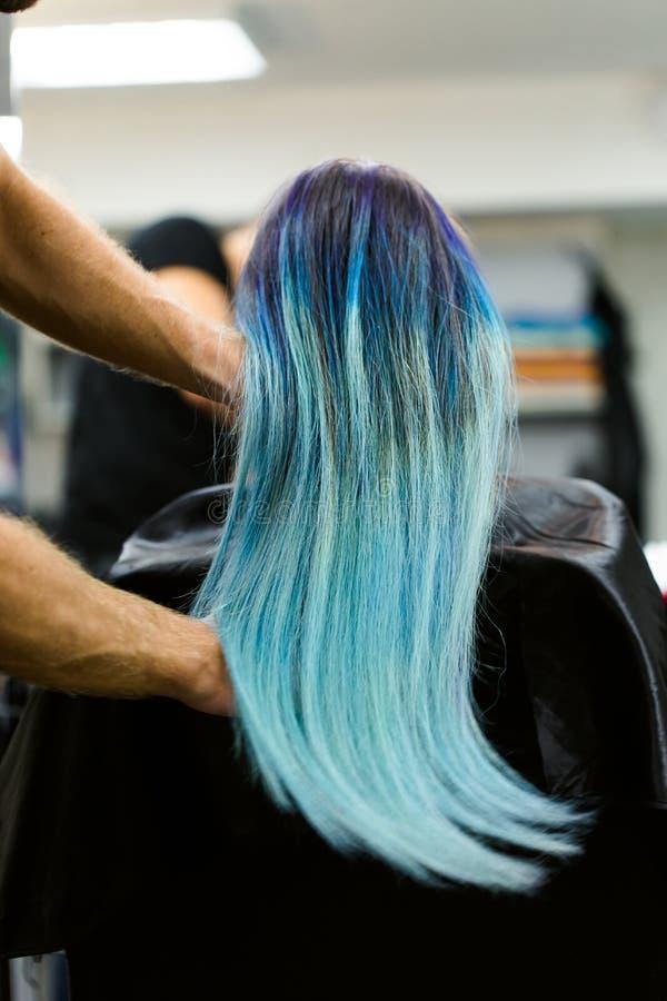 Dziewczyna z farbującym włosianym obsiadaniem w krześle przy piękno salonu studiiem Praca nad demonstracją obraz royalty free