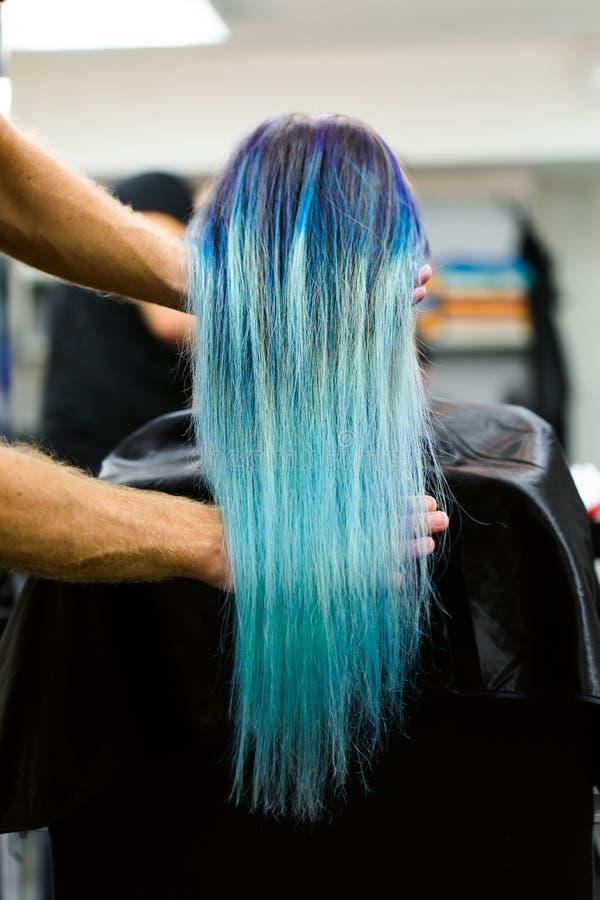 Dziewczyna z farbującym włosianym obsiadaniem w krześle przy piękno salonu studiiem Praca nad demonstracją fotografia stock