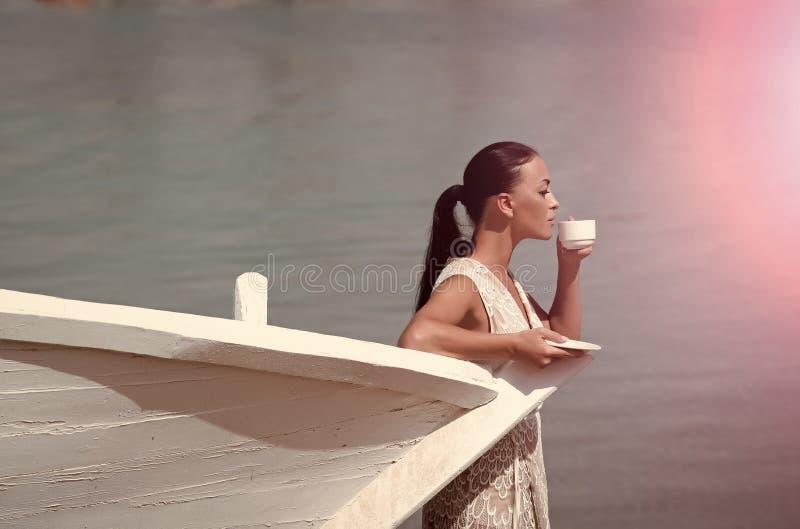 Dziewczyna z filiżanką przy łodzią zdjęcia royalty free