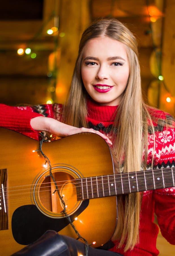 Dziewczyna z gitarą akustyczną w świątecznym środowisku obraz royalty free