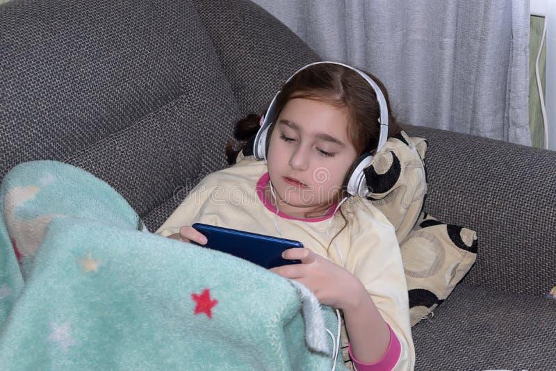 Dziewczyna z hełmofonami bawić się w telefonie zdjęcia royalty free