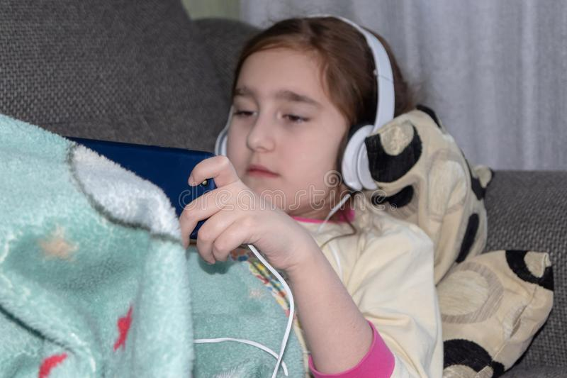 Dziewczyna z hełmofonami bawić się w telefonie obrazy stock
