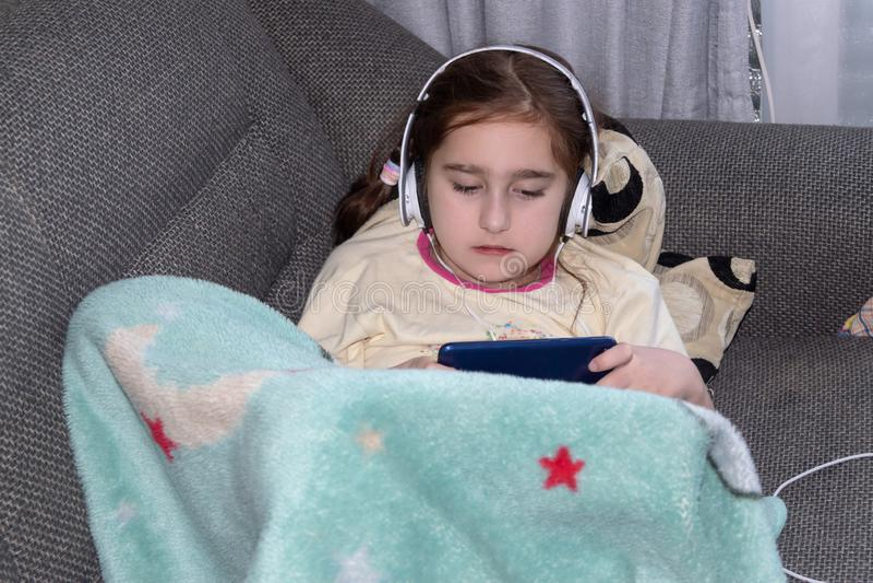 Dziewczyna z hełmofonami bawić się w telefonie fotografia royalty free
