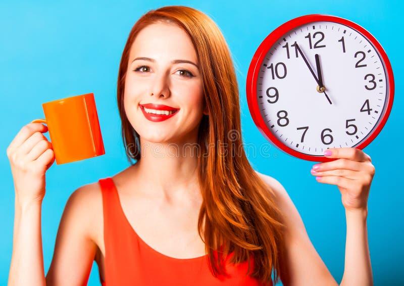 Dziewczyna z herbacianą filiżanką i ogromnym zegarem obraz royalty free