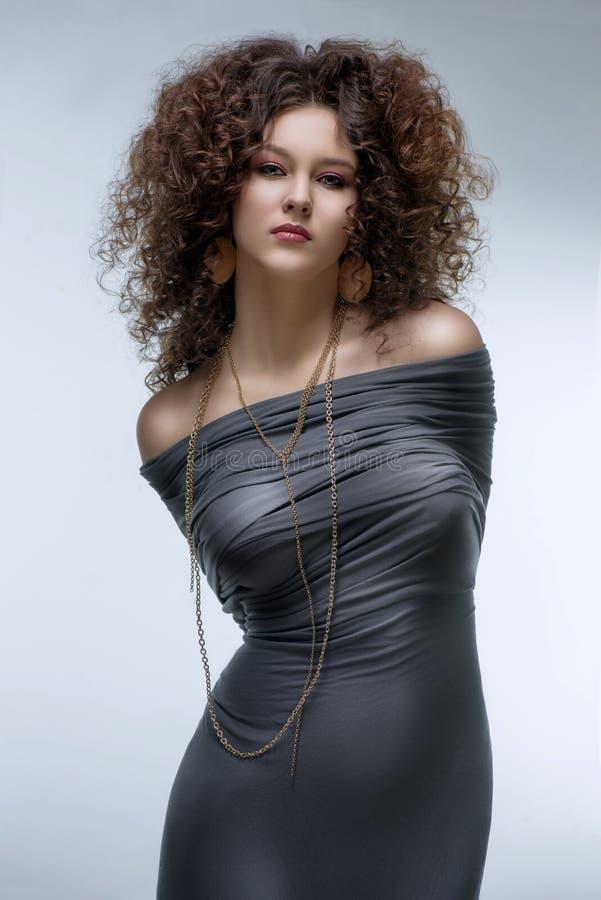 Dziewczyna z kędzierzawą fryzurą, nowożytnym makijażem i carnivore spojrzeniem, fotografia stock