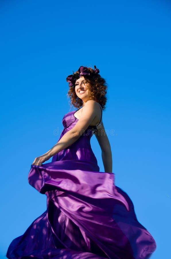 Dziewczyna z kędzierzawego włosy lataniem w purpurowej sukni obraz stock