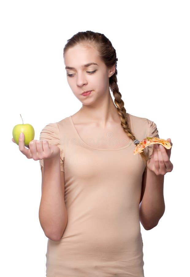 Dziewczyna z kawałkiem pizza i zieleni jabłko fotografia royalty free