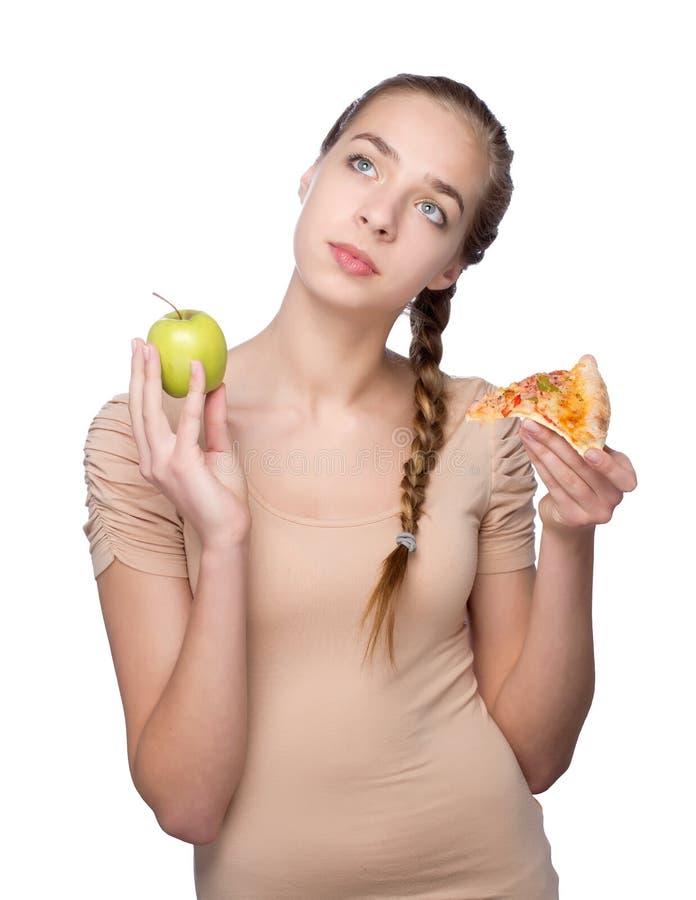 Dziewczyna z kawałkiem pizza i zieleni jabłko obraz royalty free