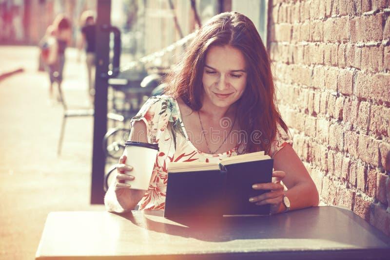 Dziewczyna z kawową czytelniczą książką fotografia stock