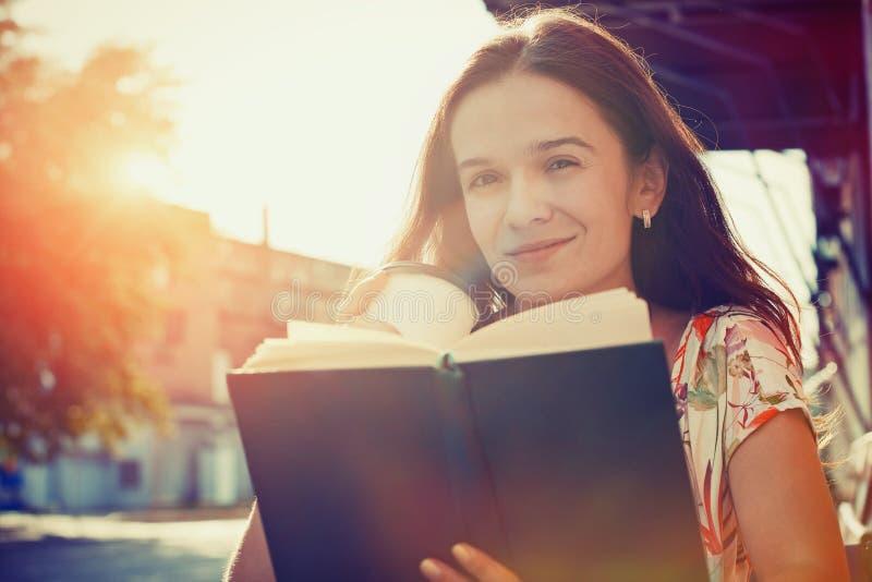 Dziewczyna z kawową czytelniczą książką obraz royalty free