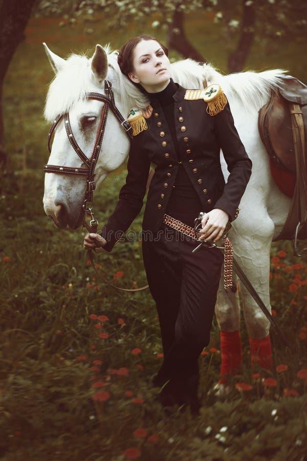 Dziewczyna z kordzikiem od bajka stojaków obok białego konia zdjęcie stock