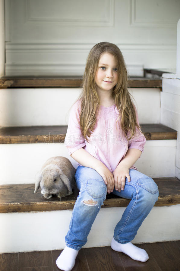 Dziewczyna z królika obsiadaniem na schodkach w domu fotografia royalty free