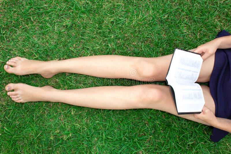 Dziewczyna z książką siedzi na trawie Piękne długie szczupłe kobiet nogi obrazy royalty free