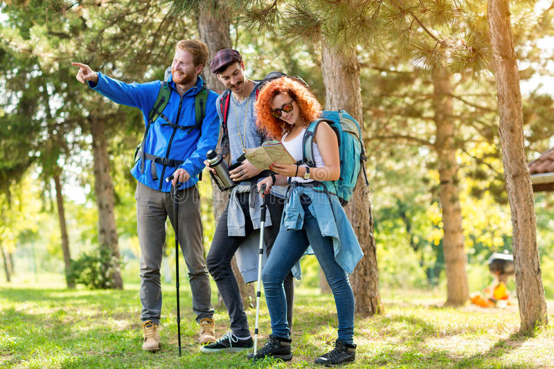 Dziewczyna z kumpel spojrzeniem przy mapą w lesie obraz royalty free