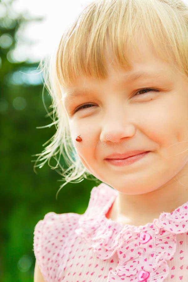 Dziewczyna z ladybird na jej policzku fotografia royalty free