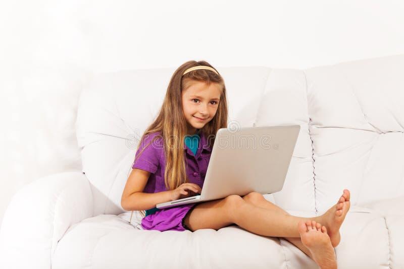 Dziewczyna z laptopem na leżance fotografia stock