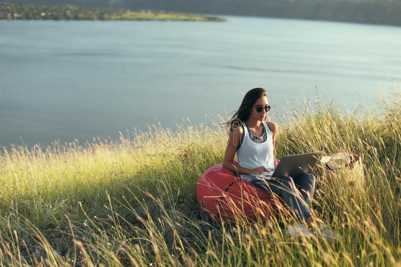 Dziewczyna z laptopem na wybrzeżu w świetle słonecznym zdjęcia royalty free