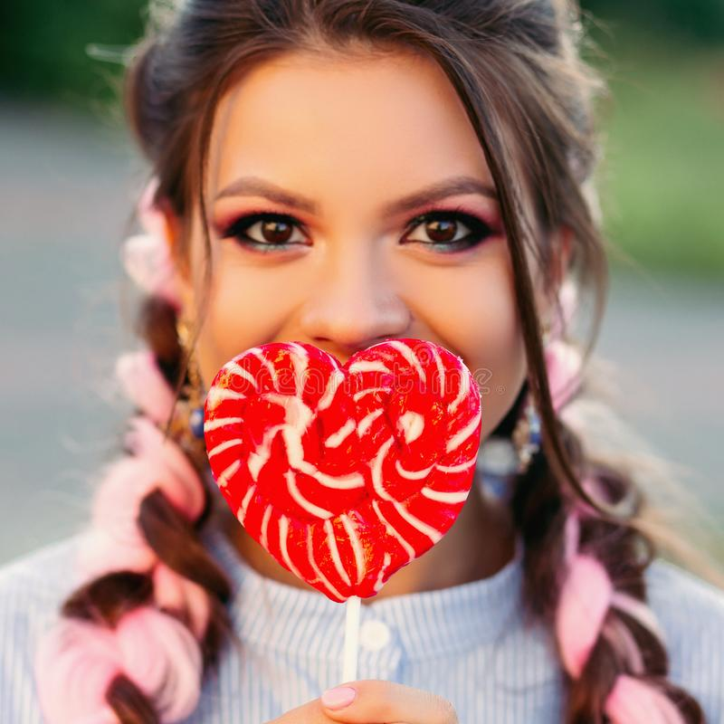 Dziewczyna z lizakiem Piękno splendoru modela kobieta z modnych włosianych mienie menchii lizaka słodkim kolorowym cukierkiem zdjęcie stock